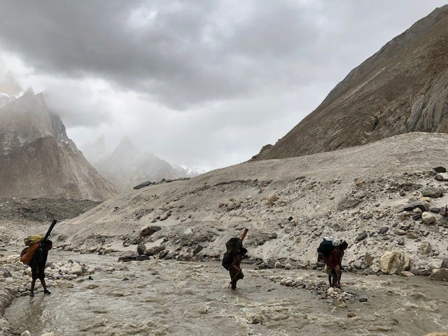 Porters crossing the ice cold glacial river on the way to Khobutse