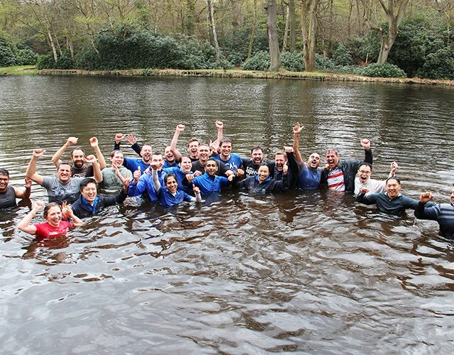 Photo of participants smiling and cheering whilst swimming in a lake at the end of the obstacle course